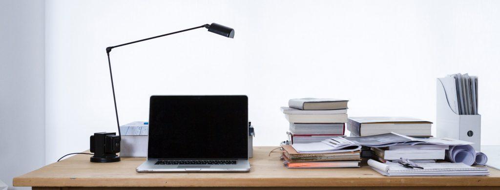 Laptop next to stacks of books
